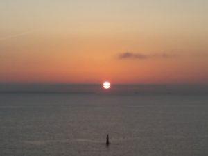 地平線の雲に切られた太陽